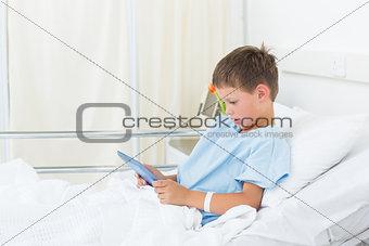 Little boy using digital tablet in hospital
