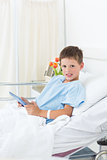 Sick boy holding digital tablet in hospital