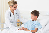 Doctor examining sick boy in hospital