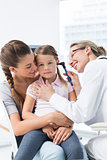 Girl being examined by pediatrician with otoscope