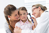 Girl being examined by doctor with otoscope