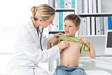 Doctor examining boy with stethoscope