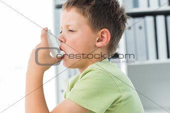Boy using an asthma inhaler in clinic