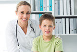 Friendly doctor with boy in clinic