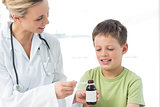 Pediatrician giving little boy syrup