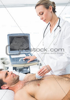 Cardiologist giving heart ultrasound to patient