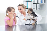 Vet with girl examining puppy