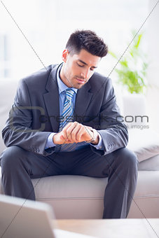 Smiling businessman sitting on the sofa checking his watch
