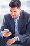 Businessman sitting on sofa sending a text