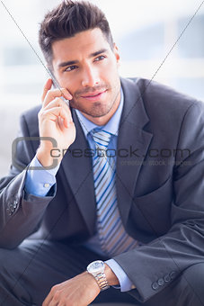 Happy businessman sitting on sofa making a call