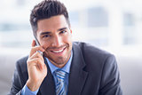 Handsome businessman sitting on sofa making a call smiling at camera