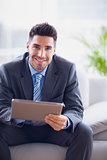 Businessman sitting on sofa using his tablet pc smiling at camera