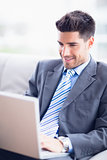 Businessman sitting on sofa using his laptop