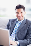 Happy businessman sitting on sofa using his laptop
