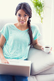 Pretty girl sitting on a sofa using laptop smiling at camera