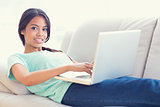 Pretty girl lying on sofa using her laptop smiling at camera