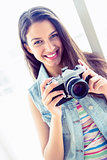 Smiling young woman holding her camera