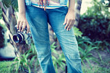 Woman wearing jeans holding camera outside