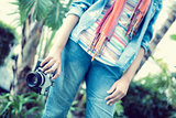 Woman wearing jeans and denim shirt holding camera outside