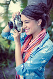 Cheerful brunette taking a photo outside