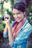 Cheerful brunette taking a photo outside smiling at camera