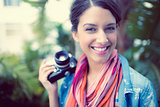 Cheerful brunette photographer standing outside smiling at camera