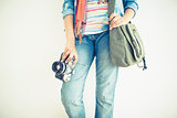 Woman in jeans holding camera and shoulder bag