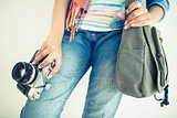 Woman in denim holding camera and shoulder bag