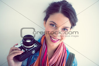Attractive brunette holding camera smiling