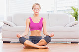 Slim blonde meditating in lotus pose