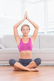 Calm blonde meditating in lotus pose with arms raised