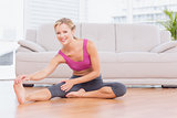 Smiling blonde sitting on floor stretching her leg