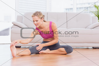 Fit blonde sitting on floor stretching her leg