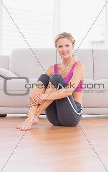 Slim blonde sitting on floor smiling at camera