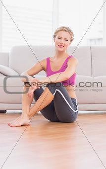 Athletic blonde sitting on floor smiling at camera