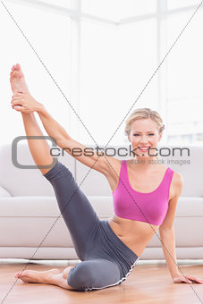 Athletic blonde sitting on floor stretching leg up smiling at camera
