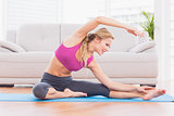 Fit blonde stretching on exercise mat