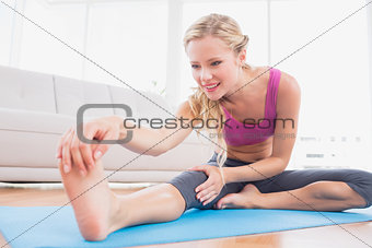 Toned blonde stretching on exercise mat