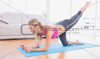 Toned blonde doing pilates on exercise mat