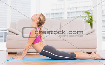 Fit blonde doing yoga on exercise mat