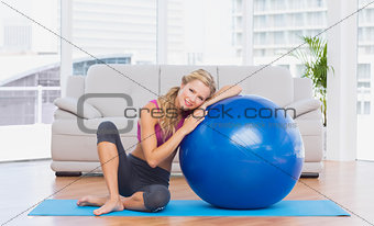 Toned blonde sitting beside exercise ball smiling at camera