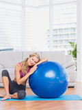 Fit blonde sitting beside exercise ball smiling at camera