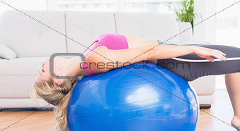 Slim blonde stretching her back on exercise ball