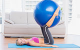 Slim blonde holding exercise ball between legs