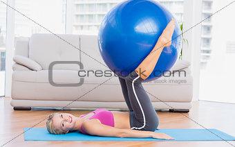 Slim blonde holding exercise ball between legs