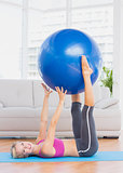 Happy blonde holding exercise ball between legs