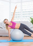 Happy fit blonde doing side plank with exercise ball