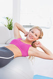 Smiling fit blonde doing sit ups with exercise ball