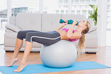 Smiling blonde doing sit ups with exercise ball holding dumbbells