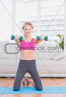 Smiling blonde lifting dumbbells on exercise mat